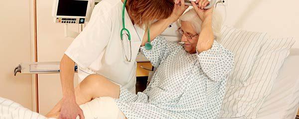 Krankenschwester hilft Patientin aus dem Bett