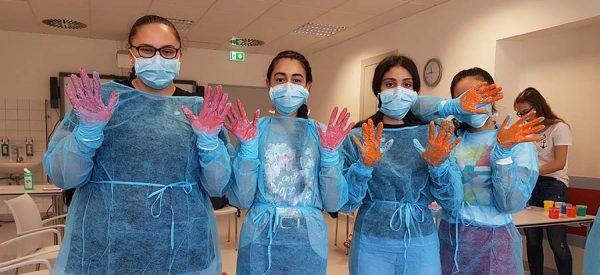 Schüler bei einer Station mit Fingerfarben zur Keimsimulation