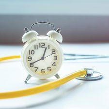 Wecker und Stethoskop. Was gehört in der Pflege zur Arbeitszeit?