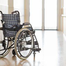 Rollstuhl steht in einem Flur mit Handläufen