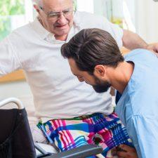 Pflegeassistent hilft Senior in Rollstuhl