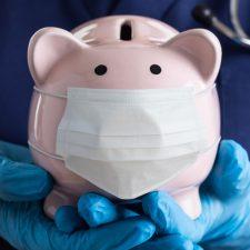 Sonderprämie: Pflegekraft hält Sparschwein mit Mundschutz