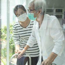 Frau begleitet Seniorin mit Gehhilfe vor Fensterfront
