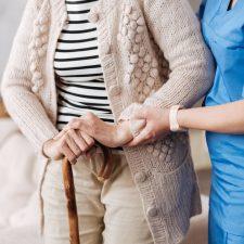 Pflegekraft stützt Heimbewohnerin
