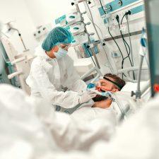 Pflegekraft mit Schutzanzug setzt Coronapatient Ventialtionsmaske auf