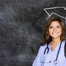 Junge Krankenschwester vor schwarzer Tafel mit aufgemaltem Magiserhut