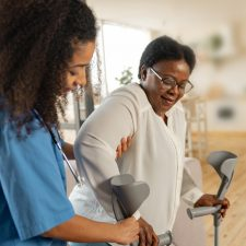 Pflegekraft stützt Frau und reicht ihr Krücken