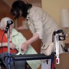 Seniorin mit Rollator erhält im Pflegeheim Hilfe beim Anziehen