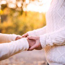 Zwei Personen, die sich an der Hand halten