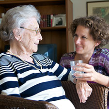 Eine junge Frau reicht ihrer älteren Mutter ein Glas Wasser