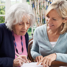ältere dame füllt im beisein ihrer tochter ein schreiben aus