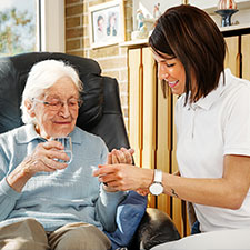 Eine junge Dame gibt einer älteren Frau ein Glas Wasser sowie ihre Medikamente