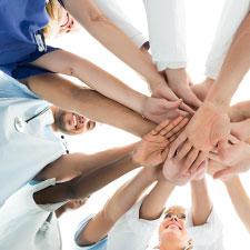 Personen aus der Pflege legen ihre Hände in der Mitte übereinander