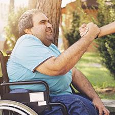 Mann im Rollstuhl erhält wertschätzenden Handschlag von seinem Pfleger